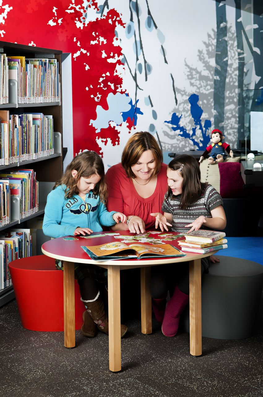 Children and women reading a book at the library